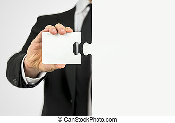 Businessman with a piece of the puzzle standing ready to fit...