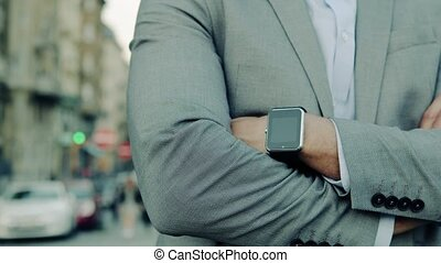 Businessman with a smartwatch in a city.
