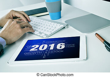 businessman with a tag cloud of goals for the 2016 in his tablet