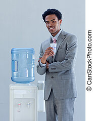 Afro-American businessman with a water cooler in office