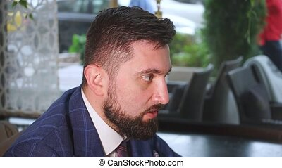 handsome businessman with accurate brown beard in expensive blue jacket holds conference in restaurant closeup slow motion