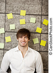 Businessman With Adhesive Notes On Wooden Wall