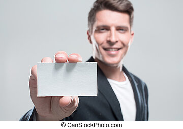 Businessman with arm out in a welcoming gesture over gray backgr