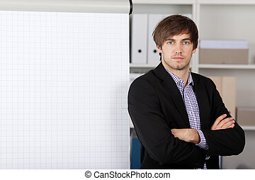 Businessman With Arms Crossed In Front Of Flip Chart