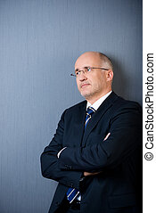 Businessman With Arms Crossed Looking Away Against Blue Wall