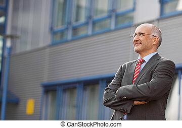 Businessman With Arms Crossed Standing Against Office