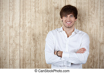 Businessman With Arms Crossed Standing Against Wooden Wall