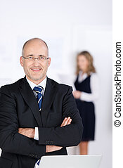 Businessman With Arms Crossed Standing In Office