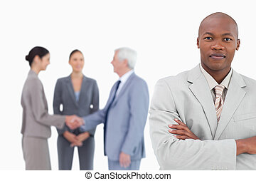 Businessman with arms folded and trading partners behind him