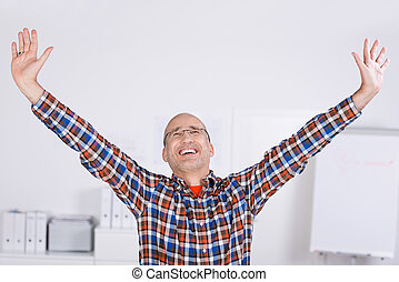 Businessman With Arms Raised Celebrating Victory In Office