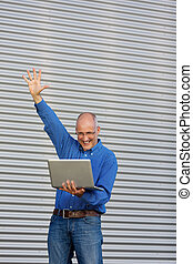 Businessman With Arms Raised Holding Laptop Against Shutter
