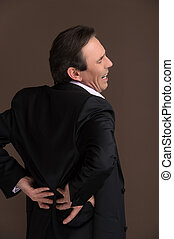 Businessman with backache. Mature businessman suffering from backache on brown background