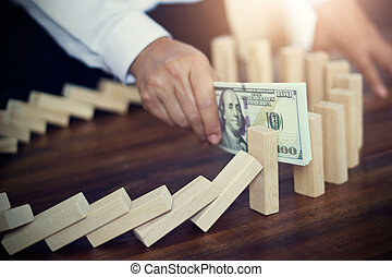 Businessman with banknote in hand stopping the domino effect of business, strategy and successful business intervention, abstract symbol