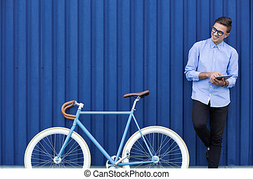 Businessman with bicycle and tablet