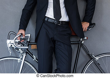Businessman with bicycle. Close-up of businessman leaning at...