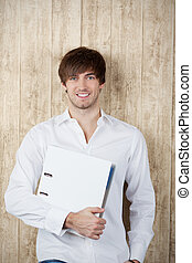 Businessman With Binder Against Wooden Wall