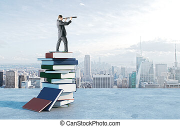 Businessman with binoculars standing on book