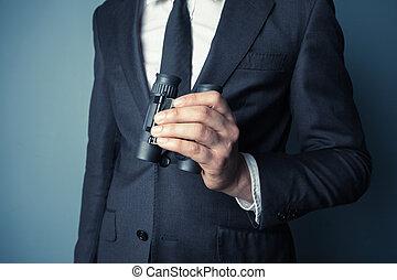 Businessman with binoculars - Businessman is holding...
