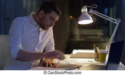 businessman with blueprint and laptop at night - business,...