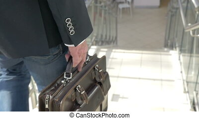Businessman with briefcase going downstairs - Slow motion,...