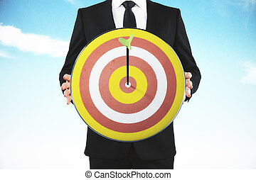 Businessman with bull's-eye and arrow at blue sky background