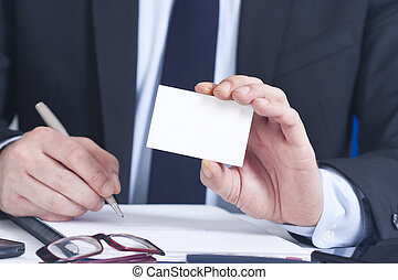 businessman with business card in foreground