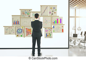 Businessman with business concept scheme on posters on white wall