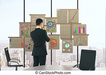 Businessman with business scheme concept posters on the window in conference room