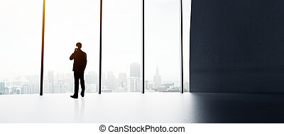 businessman with cell phone in big sunlight office