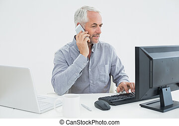 Businessman with cellphone, laptop and computer at desk -...