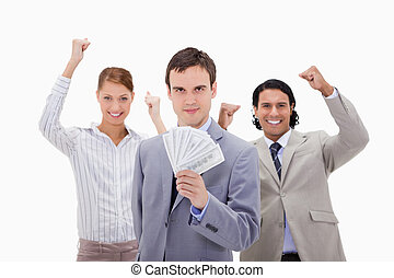 Businessman with cheering colleagues and money against a...