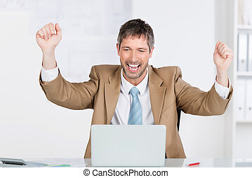Businessman With Clenched Fists Celebrating Victory At Desk