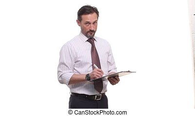 serious and confident businessman filling application form and writing data on sheet of paper and looking at camera. Handsome bearded man offering and suggesting clipboard to camera in studio.