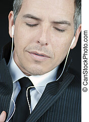 Businessman With Closed Eyes Wearing Headphones