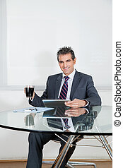 Businessman With Coffee Cup Using Digital Tablet In Office