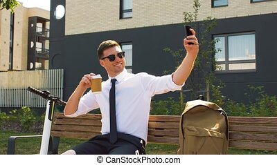businessman with coffee takes selfie by smartphone -...