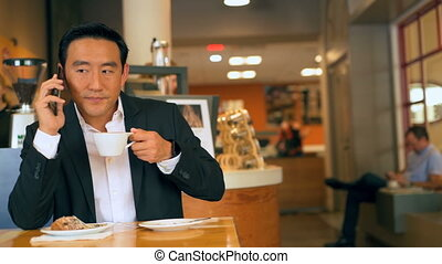 Businessman with coffee while talking on mobile phone 4k