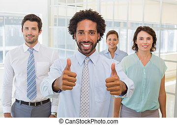 Businessman with colleagues gesturing thumbs up in office