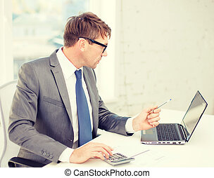 businessman with computer, papers and calculator