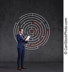 Businessman with computer tablet standing on a labyrinth background. Business, strategy, concept.