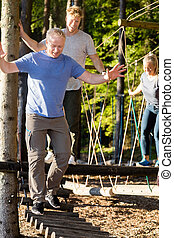 Businessman With Coworkers Crossing Log Bridge In Forest