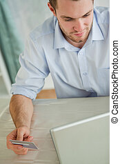 Businessman with credit card on his laptop
