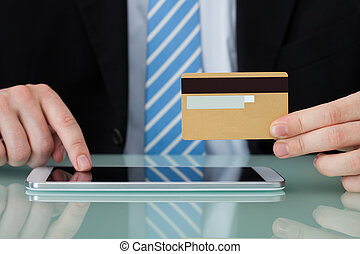 Businessman With Credit Card Using Digital Tablet