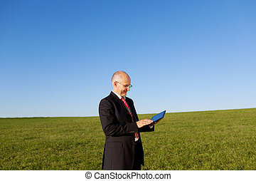 Businessman With Digital Tablet Against Sky