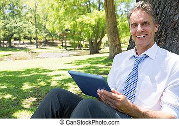 Businessman with digital tablet in park