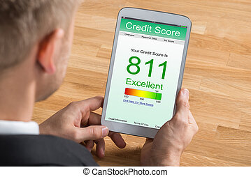 Businessman With Digital Tablet Showing Credit Score