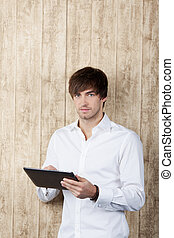 Businessman With Digital Tablet Standing Against Wood