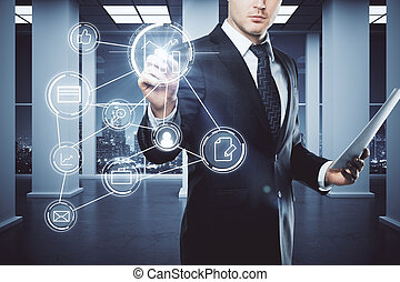 Businessman with document in hand drawing glowing business icons in concrete office interior with night city view. Digital concept. 3D Rendering