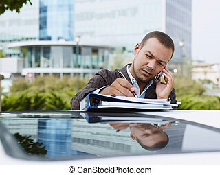 Businessman With Documents On Car Roof Takes Notes Of Phone Call
