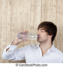Businessman With Drinking Water From Bottle Against Wooden Wall